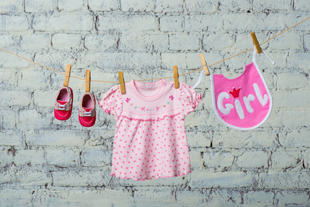 Childrens bib, dress and red shoes for the girl, dry on a rope on a white brick wall.