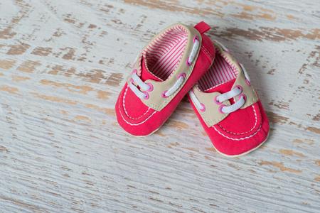 Zapatos rojos del bebé en una cuerda contra una pared de ladrillo blanca.