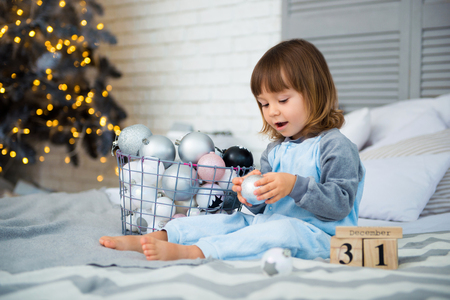Small cute little girl is 2 years old sitting near Christmas tree and looking at the calendar. 31th of December.