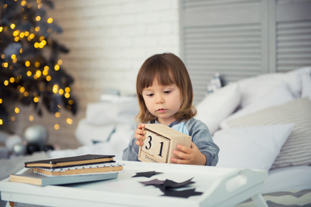 Emotional smiling little girl sitting in pajama with Christmas gifts near New Years tree and playing snowballs