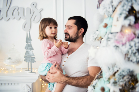 Little daughter and father near Christmas tree. Happy New Year Stock Photo
