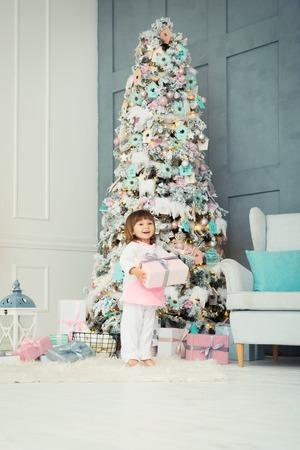 Verrukking voor kinderen. Kleine twee-jarige meisje is blij in de buurt van de kerstboom. Nieuwjaar is binnenkort. Stockfoto