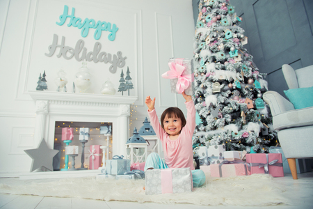 Positive cheerful baby girl sitting with Christmas gift near Christmas tree. Happy New Year Reklamní fotografie