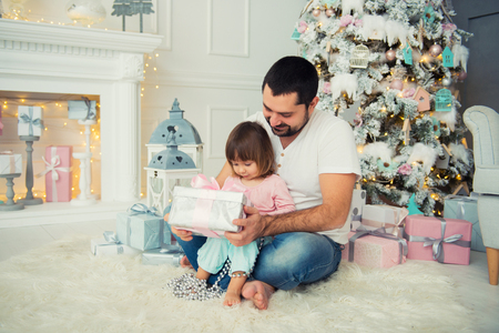 Big father and happy little daughter open New Years gifts near the Christmas tree