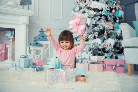 Little baby girl opens New Year gift near Christmas tree