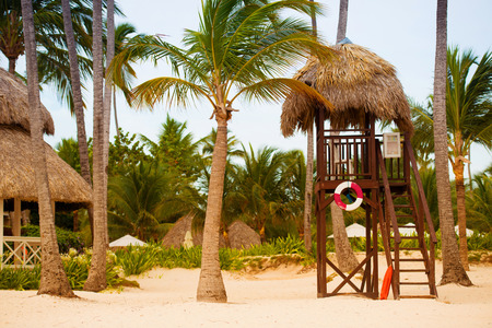 Lifeguard tower on the beach on a background of palm trees