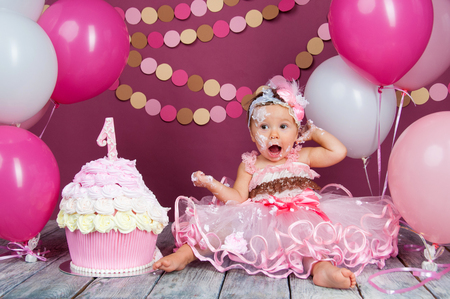 Portrait of a little cheerful birthday girl with the first cake. Eating the first cake. Smash cake Stockfoto