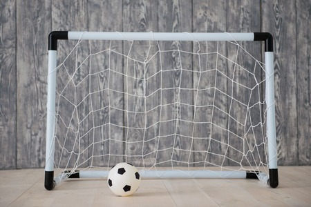 A soccer ball in a small gate on a gray background. Mini football Stock Photo