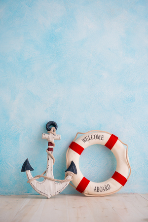 A composition on a sea theme with an anchor and lifebuoy on a blue wall. Stock Photo
