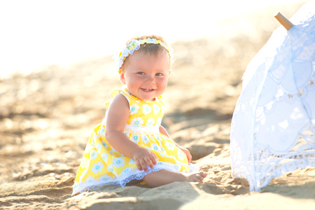 Lovely little girl on the beach with an umbrella. Stockfoto