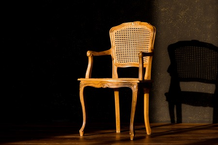old chair on a black gray wall background