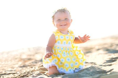 Lovely little girl on the beach with an umbrella