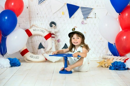 The small captain sits on the floor in a marine style. We mark the first year. Banco de Imagens - 103914059