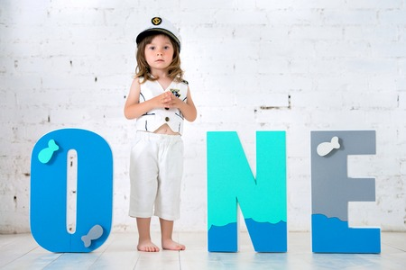Happy child in a captains suit with the letters One on a white background of a brick wall