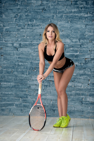 Portrait of a beautiful girl girl with a racket, a gray brick wall background.