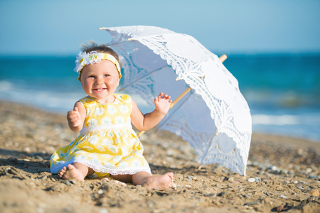 Lovely little girl on the beach with an umbrella