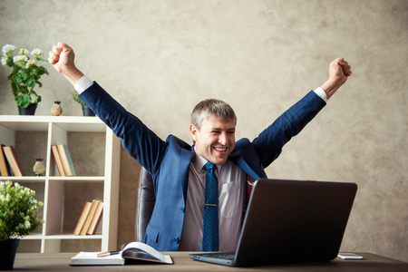 Happy excited young businessman sitting on workplace and celebrating success.