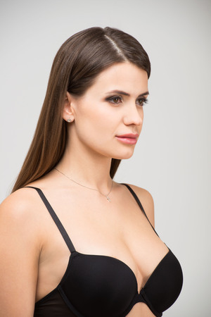 Close up portrait of beautiful brunette women with a slim figure in black bra. Model snaps in the studio on white background.