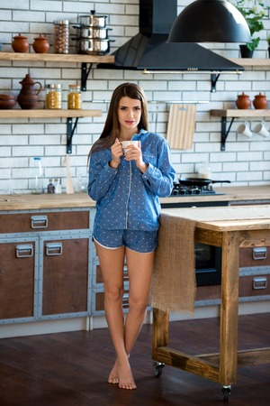 Full height portrait of a young woman with a cup of tea or coffee in blue pajamas in the kitchen. Morning lifestyle. Stock Photo