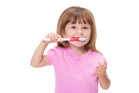 Close-up portrait Cute little girl 3 year old in pink t-shirt brushing her teeth isolated on white background. Фото со стока