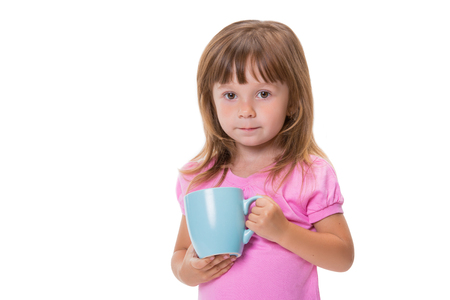 Cute three year old girl drinks water from a cup isolated on white background.