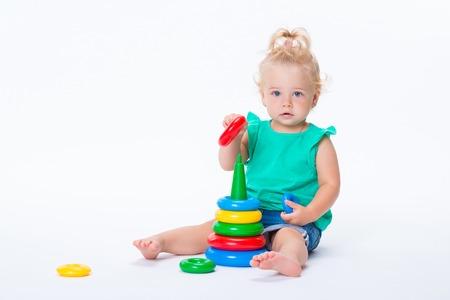 Fille blonde mignonne d'enfant jouant avec le jouet de pyramide de couleur d'isolement sur le fond blanc. Enfance heureuse et développement préscolaire des enfants.