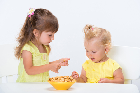 Two cute little girls sisters in yellow t-shirts eating cereal flakes at the table isolated on white background. Stock Photo