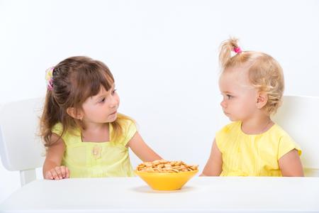 Twee schattige kleine meisjes zusters in gele t-shirts granen vlokken eten aan de tafel geïsoleerd op een witte achtergrond. Stockfoto