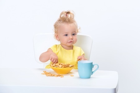 little blonde baby girl 1 year old in yellow t-shirt eating cereal flakes and drinking a cup of milk tea at the table isolated on white background.
