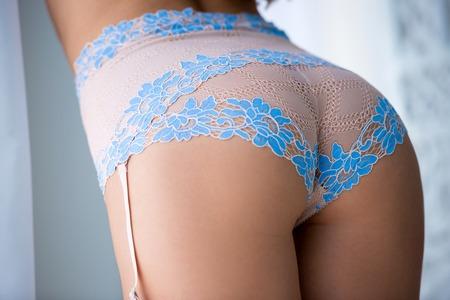 Close-up half gedraaid van ideale elastische onberispelijke mooie vrouw die blauwe onderkleding draagt, met vertrouwen met maandverband.