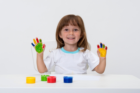 Close-up portrait of a cute cheerful happy smiling little girl draws her own hands with gouache or finger paints isolated on white background.