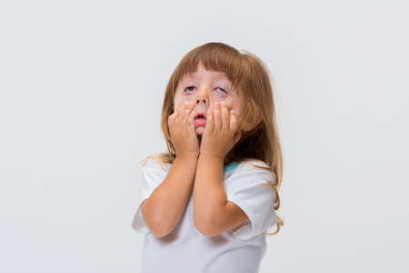 Close-up portrait of little girl's face isolated on white background. Girl grimacing, covering her face with her hands.