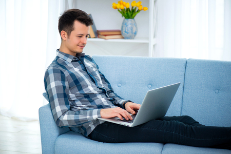 A Young attractive guy man is browsing at his laptop, sitting at home on the cozy blue sofa at home, wearing casual outfit.