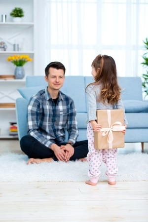 Cute little girl, daughter, sister gives a gift box to young dad father or brother. Both are smiling. Fathers day holiday concept, Childrens Day. Stock Photo