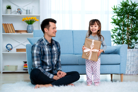 Father and daughter or brother and sister with a gift in the interior of the room. Fathers day holiday concept, Childrens Day. Stock Photo