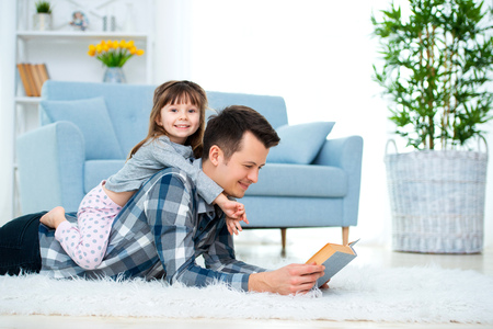 Happy family and father's day concept. Dad with daughter spending time togetherness at home. Cute little girl on dad's back lying on warm floor. Imagens