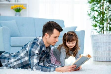 Cute little girl listening to dad reading fairy tale lying on warm floor together, caring father holding book , family hobbies activities at home. 版權商用圖片