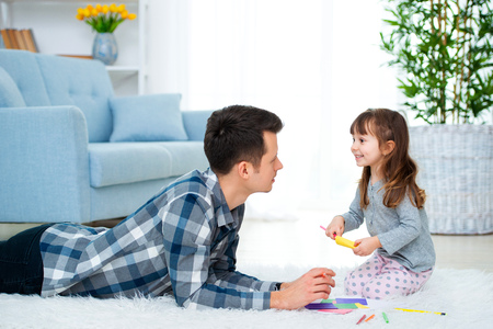 father and little daughter having quality family time together at home. dad with girl lying on warm floor drawing with colorful felt tip pencils. 版權商用圖片