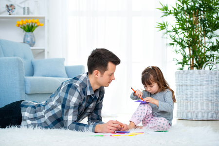 father and little daughter having quality family time together at home. dad with girl lying on warm floor drawing with colorful felt tip pencils. Reklamní fotografie