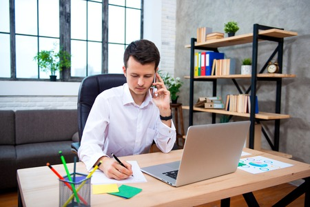 Successful businessman talking on phone using laptop sitting at office, young entrepreneur man speaking by cell and takes notes.