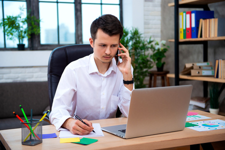 Successful businessman talking on phone using laptop sitting at office, young entrepreneur man speaking by cell and takes notes. Banco de Imagens