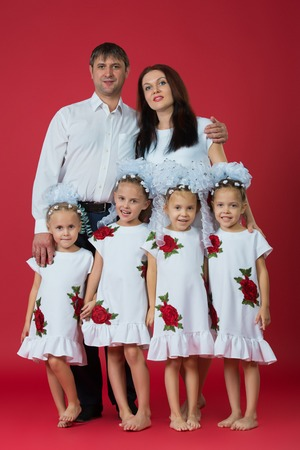 Big happy family: parents are father, mother and children are twins in embroidered dresses with an ornament on a red background in the studio