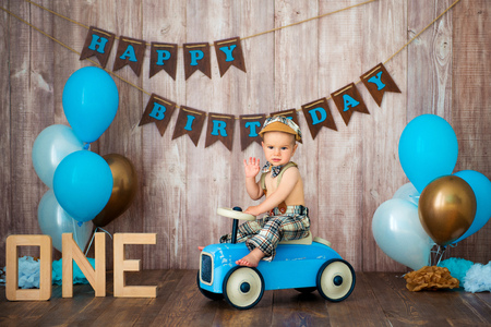 Little boy kid gentleman in retro costume with suspenders and cap is sitting on a wooden car. Children's party with balloons Happy Birthday, 1 year.