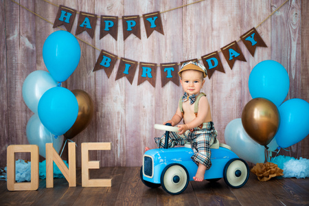 Little boy kid gentleman in retro costume with suspenders and cap is sitting on a wooden car. Childrens party with balloons Happy Birthday, 1 year.