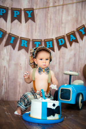 Photoshoot crush smashcake for a little boy gentleman. Decorated photozone with a wooden retro car and helium balloons. Happy birthday, 1 year. Archivio Fotografico