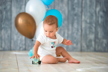 Cute little boy 1 year old sits on a warm wooden floor and plays with a toy car. Behind the plan birthday balloons.