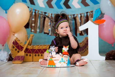 Little cute girl in costume of Apache Indian chief and in a feather headdress sits and tastes a sweet cake. First birthday 1 year and smash cake. Reklamní fotografie