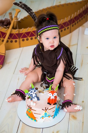 Little cute girl in costume of Apache Indian chief and in a feather headdress sits and tastes a sweet cake. First birthday 1 year and smash cake.