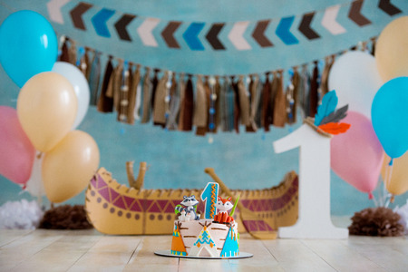 Decorated photo zone for 1 year Indian Apache chief with a canoe for a childrens party. First birthday and smash cake.
