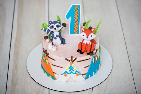 Close up of cake from pastry chef for birthday 1 year old baby. Childrens cake is decorated with animal figures, wigwam and number one. Stock Photo